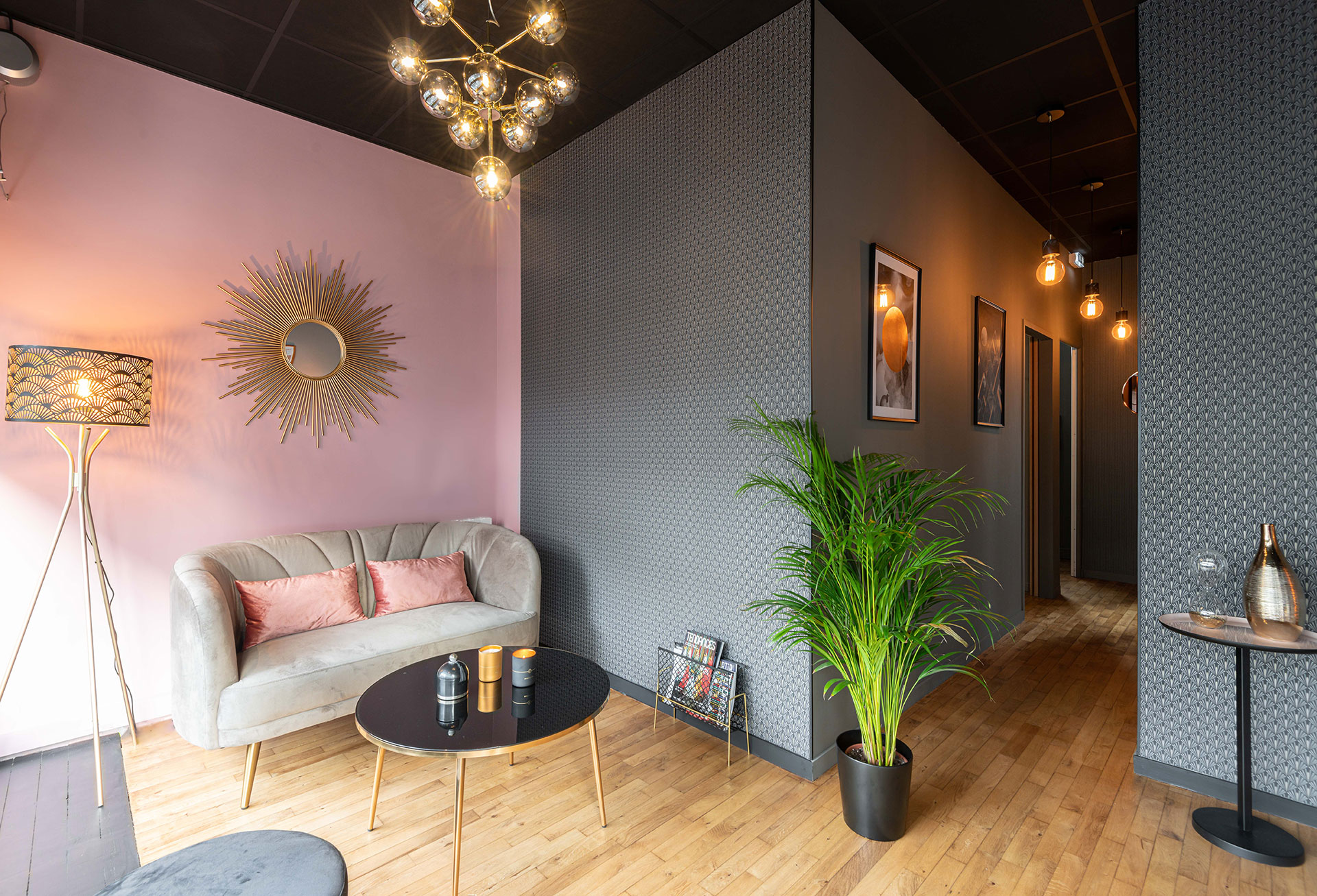 Ambiance et rénovation pour un institut de beauté à Lorient, Agence BFB Lorient et Ile de Ré, salon d'accueil avec canapé gris et mur rose poudré - Papier peint noir et doré